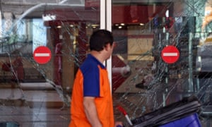A worker walks past the broken windows from the blasts at Turkey's largest airport.