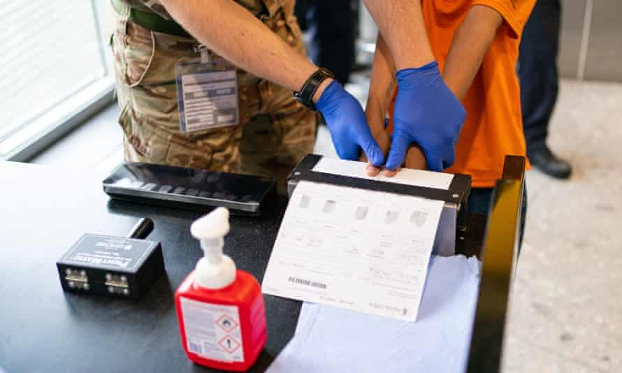 Afghan refugee has his fingerprints taken after arriving on an evacuation flight at Heathrow in August 2021