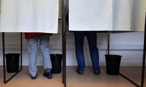 Voting booths, with voters' legs showing under drawn curtains
