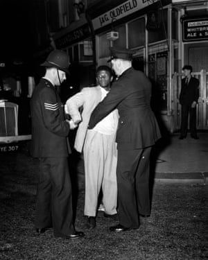 Police search a youth in Talbot Road, Notting Hill during race riots of 1958