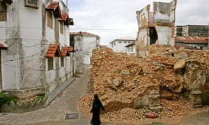 Tough going ... a woman walks past a collapsed building in Zanzibar's Stone Town.