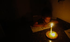 A girl reads at her house with the help of a candle during blackouts on Tuesday in Caracas.