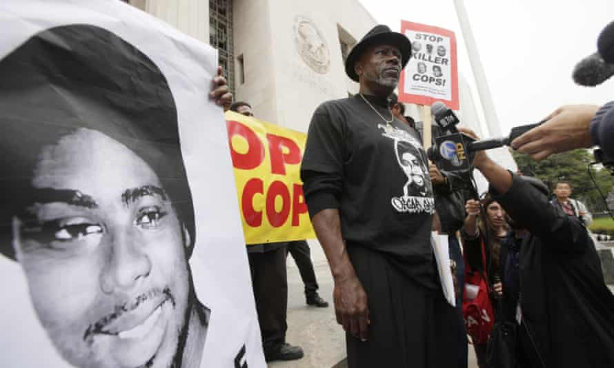In a 2011 photo, Cephus 'Bobby' Johnson stands on court steps in Los Angeles protesting the release of Johannes Mehserle, who shot Oscar Grant, Johnson's nephew.