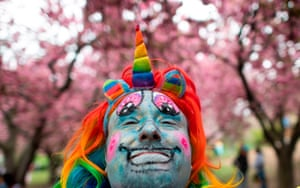New York City, US A man in a rainbow unicorn costume poses during the Cherry Blossom festival at the Botanic Garden in Brooklyn, New York