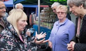 Kathy Mohan, left, gesticulates at Theresa May