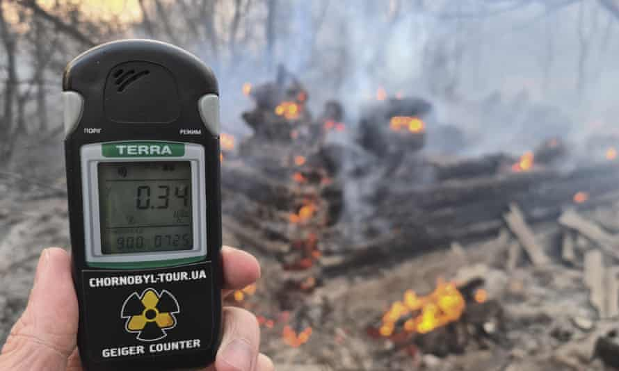 A Geiger counter shows increased radiation level at the forest fire near Chernobyl.
