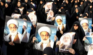Anti-government protesters hold posters of Ayatollah Isa Qassim