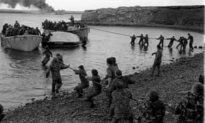 Survivors from HMS Sir Galahad are hauled ashore at Bluff Cove during the Falklands war.