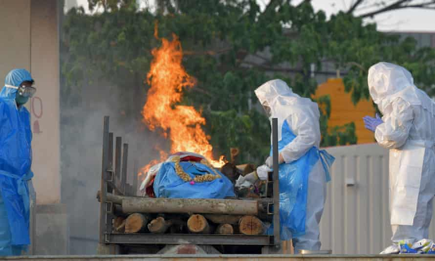 Relatives wearing protective gear perform final rites for a Covid victim at an open crematorium in Bangalore, India