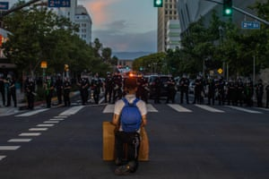A demonstrator kneels in front of a police line in downtown Los Angeles