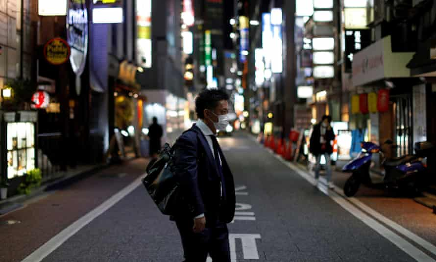 A man wearing a protective face mask, following an outbreak of the coronavirus disease, walks at Ginza shopping and amusement district in Tokyo