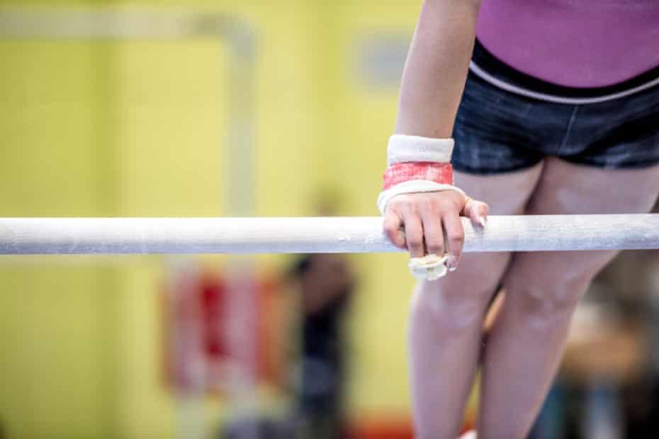 Young Woman Athlete Exercising on Horizontal Bar.