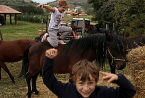 Ginevra, 10, and her younger brother Giulio Cesare play with their horses at the family farm