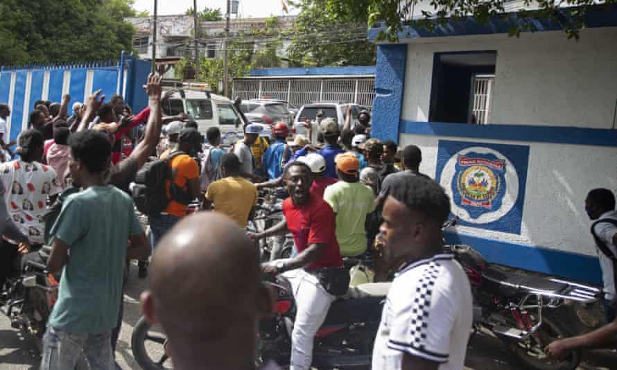 People gather outside a police station in Port-au-Prince on Thursday, one day after the assassination of President Jovenel Moïse.