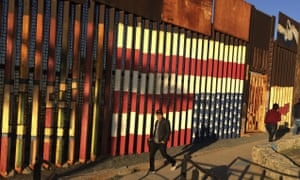 People pass graffiti along the border structure in Tijuana, Mexico on Wednesday.