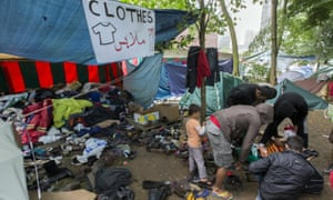 Asylum seekers search for clothes in a makeshift camp outside the foreign office in Brussels, Belgium