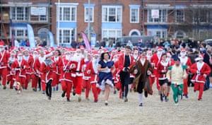 Dorset, UK: Runners dressed as Santa on Weymouth beach