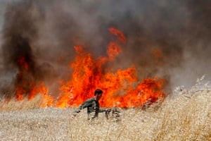 An Israeli soldier battles to extinguish a fire in a wheat field near the kibbutz of Nahal Oz, along the border with the Gaza strip