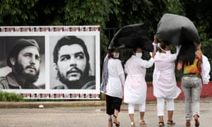 Cuban doctors, protecting themselves from the rain with plastic bags, pass by images of Fidel Castro and Che Guevara before departing to Kuwait to assist with the coronavirus outbreak, in Havana on Thursday.