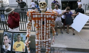 A skeleton of pill bottles with protesters outside a courthouse where a judge heard arguments in a lawsuit against Purdue Pharma in Boston, Massachusetts, on 2 August.