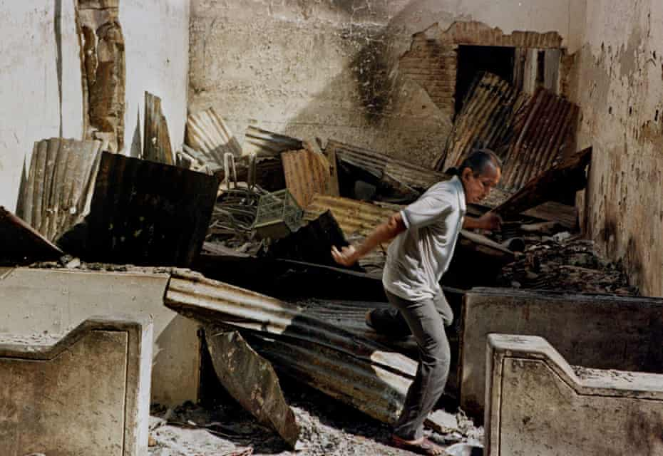 An ethnic-Chinese man jumps through the rubble of what remains of his shop after angry mobs ransacked and burned it in Glodok, north Jakarta, Sunday, May 17, 1998.