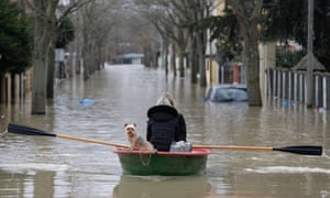 Paris residents and their dog take to the flood waters in a dinghy.