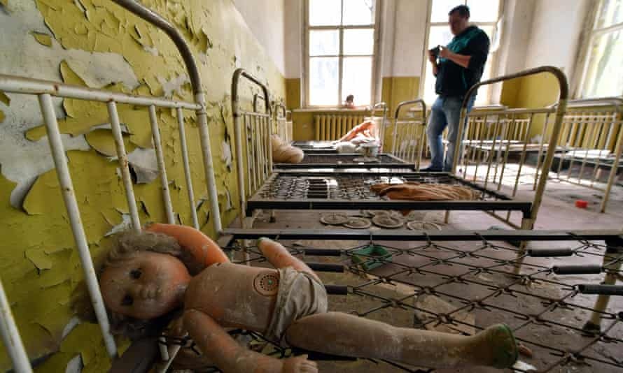 A tourist takes a picture in an abandoned kindergarten in the ghost village of Kopachi near the Chernobyl plant.