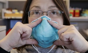 Eileen Benoliel, a Seattle and King county public health nurse, deomonstrates how to properly fit a mask.
