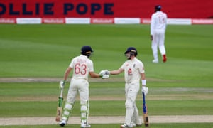 Ollie Pope is congratulated on reaching his half century by Jos Buttler, who also passed 50 before stumps.