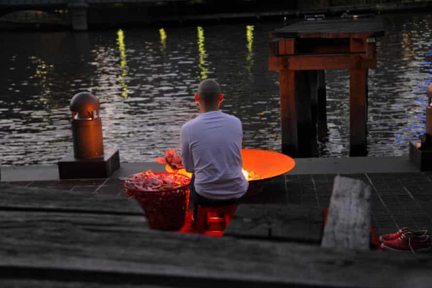 Phuong Ngo burning paper boats.