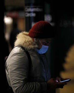 A man wears a surgical mask while waiting for a train in New York.