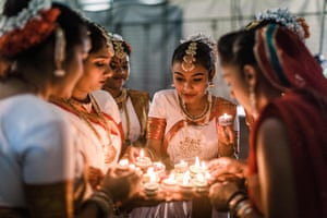 A group of dancers light colourful clay lamps in preparation to celebrate Diwali, in Durban, South Africa