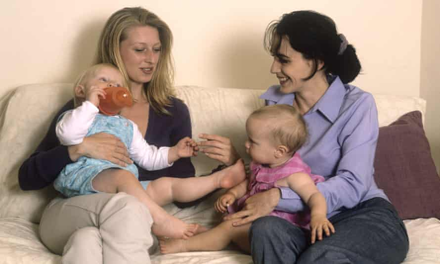 Stock image: Two mothers sitting on a sofa chatting with their toddlers
