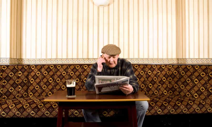 Old man reads paper in pub