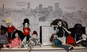 Dolls in front of an illustrated backdrop