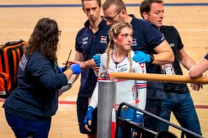 A bruised Laura Kenny is helped off the track after a crash during the women's omnium scratch race