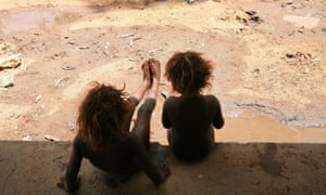 Sisters play in the mud after rare rain at a town camp on the outskirts of Alice Springs in the Northern Territory.