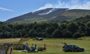 Campers set up a tent at Well-i-Hole campsite beneath Dovestones