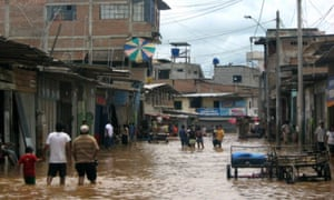 A local resident wades through the flooded streets of the village of Aguas Verdes, northern Peru, 2008