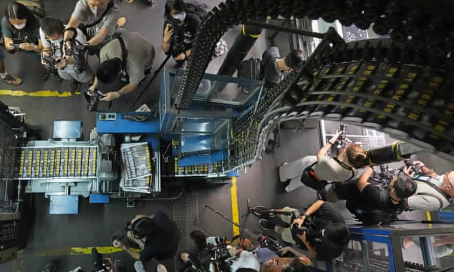 Photographers take photos of copies of Apple Daily coming off the printing press on Friday.