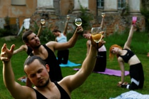 Riga, Latvia, people hold glasses of wine as they perform wine yoga