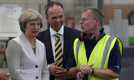 Britain's Prime Minister Theresa May (L) and housing minister Gavin Barwell (C) speak with a worker as they  visit a joinery factory in London, Britain August 3, 2016.
