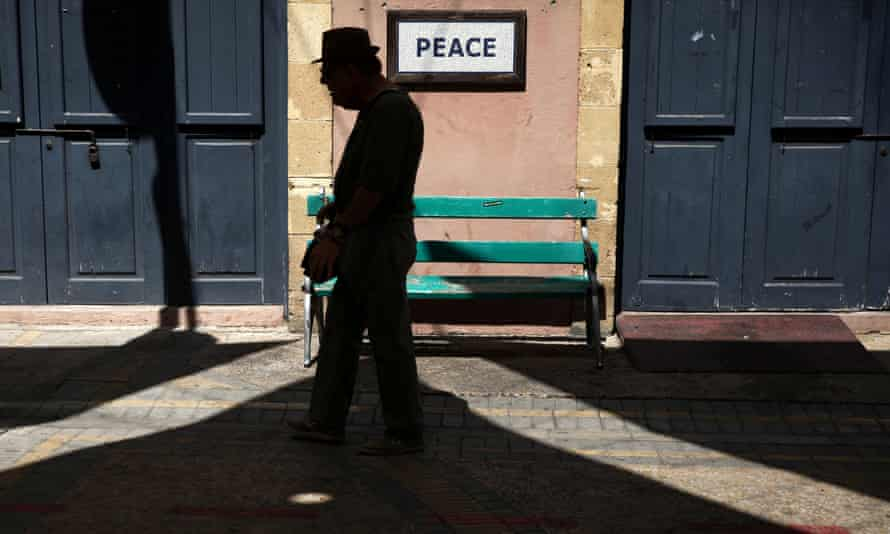 A man walks along Ledras Street past a 'peace' sign, near the UN-controlled buffer zone in Nicosia, Cyprus.