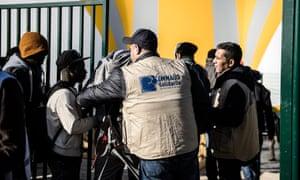 Social workers check migrants from Calais at a new centre at Porte de la Chapelle in Paris, France