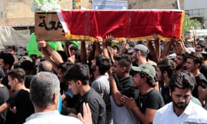 Mourners carry the coffin of a 22-year-old victim of the suicide bombing that ripped through Karada .