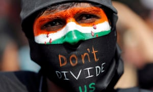 A demonstrator with face painted in Indian flag saying 'don't divide us'