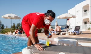 A hotel workers cleans poolside sunbeds in Ibiza