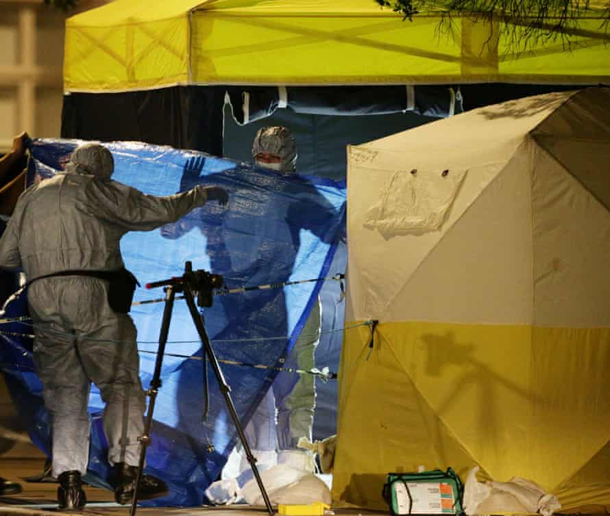 Forensic police officers examine the crime scene