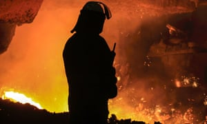 A steelworker watches as molten steel pours from a blast furnace