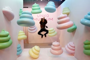 A visitor jumps to pose for a photo behind a display of poo-shaped figurines